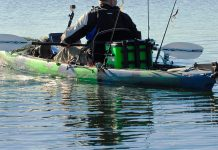 Person padding a green and black sit-on-top kayak with rods