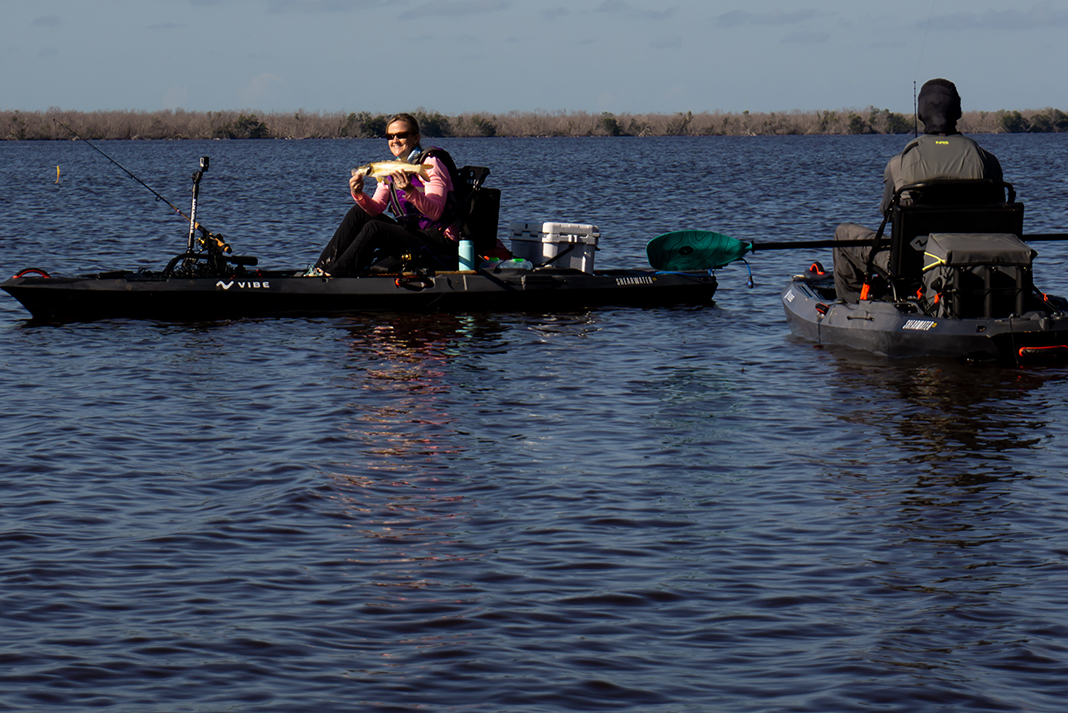 Two people on sit-on-top fishing kayaks on the ocean