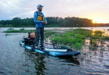 Man standing on fishing kayak and fishing