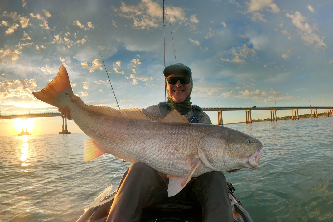 A kayak fisherman holds a large sliver fish against the backdrop of a bridge crossing the ocean.