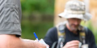 A man with a notepad in the foreground faces an angler in the background.