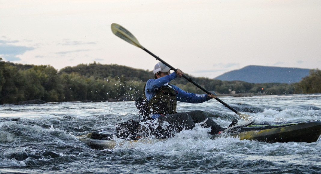 A kayak angler runs through a fast moving river.