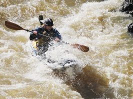 A kayak angler wearing waterproof fishing gear paddles into a big rapid.
