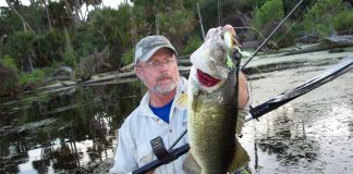 A middle aged man holds up a large bass while fishing from a kayak