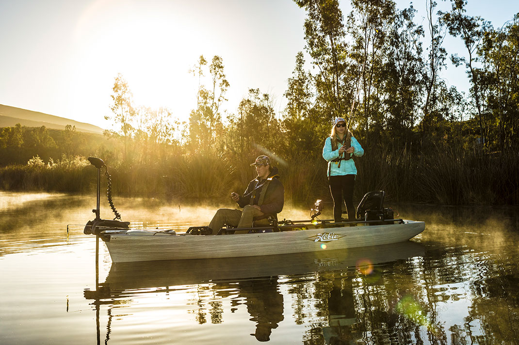 man and woman fish at dawn in a full-size Hobie fishing kayak